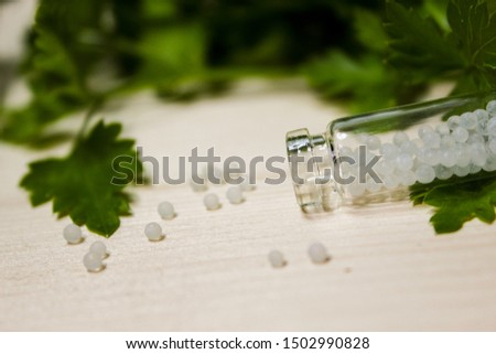 Homeopathy pills in vintage bottles on wood and green background. A bottle of homeopathic remedies #1502990828