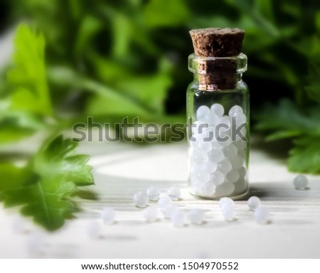 Homeopathy pills in vintage bottles on wood and green background. A bottle of homeopathic remedies #1504970552