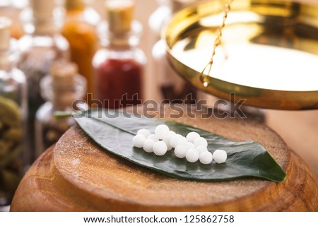 Homeopathy pills on the green leaf closeup