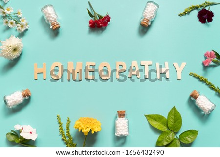 Homeopathy wooden text with homeopathic globules bottle and natural wildflowers on green backgound. Homeopathy alternative medicine concept. Flat layout. Stock photo ©