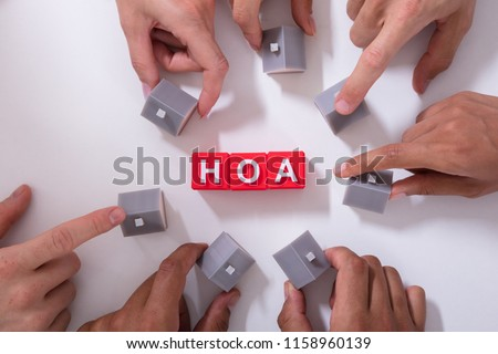Homeowner Association Blocks Surrounded By People Holding House Model On White Surface #1158960139