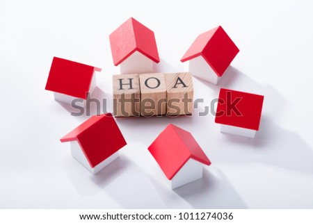 Homeowner Association Wooden Blocks Surrounded With Miniature House Models Over The White Background #1011274036