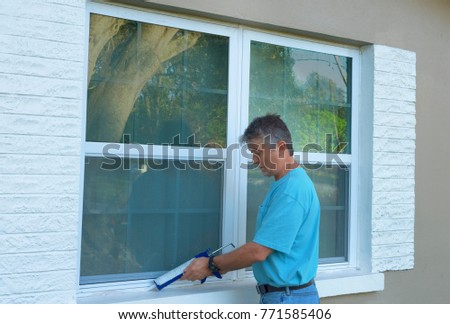 Homeowner caulking window with a caulk gun, an important part of weatherproofing homes and houses against rain, wind, hurricanes and storms and is preventive home maintenance.