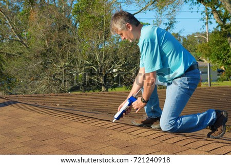 Homeowner patching roof with roof repair tar in caulk gun doing home maintenance to protect and weatherproof the house from rain, wind, storms and hurricanes.