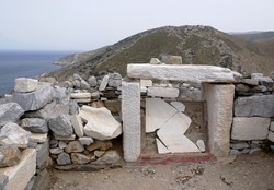 Homer the classical Greek poet. His tomb on the beautiful Greek island of Ios. Landscape view of the grave, and dramatic countryside and the Aegean sea.