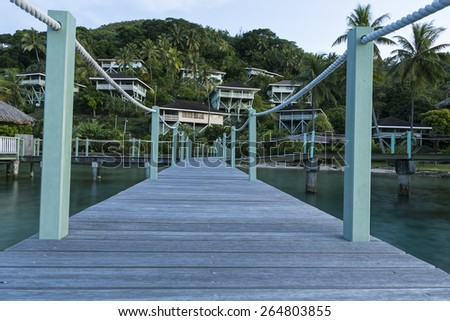 Homes on a hill with pier and water in the foreground