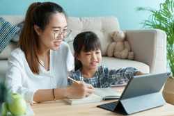 Homeschooling. Asian family with daughter doing homework by using tablet with mother help. Asia mom and child learning online with laptop computer together in the living room at home
