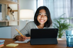Homeschooling Asian girl doing homework And study online with tablet at the desk night. Portrait of Asia child happiness and smiling confidence looking to camera
