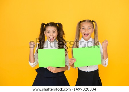 Homework done. Happy small children holding empty homework sheets on yellow background. Cute little girls smiling with blank green school posters for homework assignment. Homework, copy space.