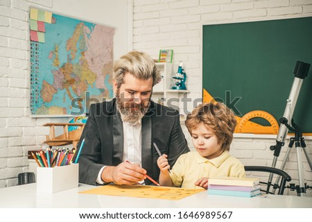 Homework help. Father helping his son to make homework. Elementary school. Pupil learning letters and numbers
