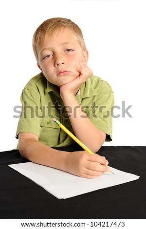 Homework Makes me Sleepy. Young boy sitting at a table looking tired or bored with his homework. Isolated on white.
