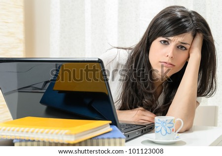 Homework problems with laptop. Upset woman with pc computer at home looking tired and frustrated. - stock photo