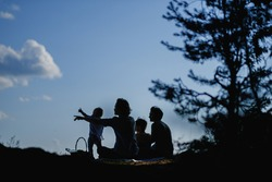 Homosexual lesbian family with two children, a son and a daughter. Two moms and kids at an outdoor picnic. Forest and sea. Summer day at sunset.