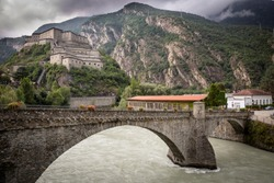 Hone/Bard old bridge over Dora Baltea river and a view of the Bard fortress, Aosta Valley, Italy