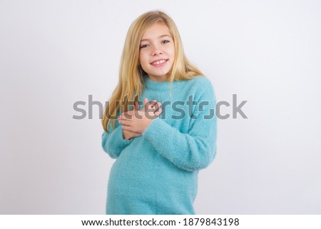 Honest cute Caucasian kid girl wearing blue knitted sweater against white wall keeps hands on chest, touched by compliment or makes promise, looks at camera with great pleasure. Photo stock ©