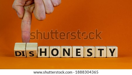 Honesty or dishonesty symbol. Businessman hand turns a cube and changes the word 'dishonesty' to 'honesty'. Beautiful orange background. Business and honesty or dishonesty concept. Copy space. Photo stock ©