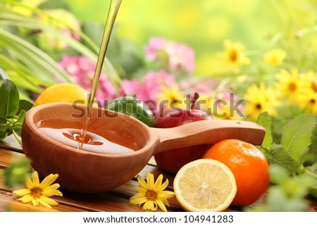 Honey and fresh fruits with flowers background,closeup.