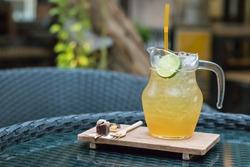 Honey and lemon iced tea with tiny dressert on the table.