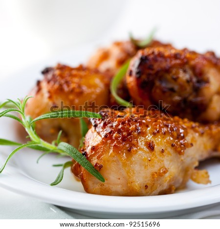 Honey and mustard glazed chicken legs. Spicy chicken legs. Baked Chicken Legs with Rosemary. Homemade food. Symbolic image. Concept for a tasty and healthy dish. Rustic wooden background. Close up