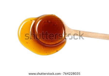 Honey and wooden spoon isolated on white background #764228035