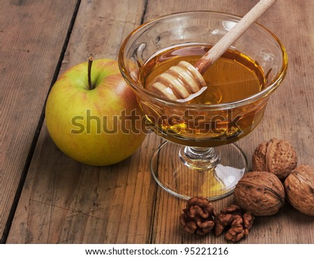 Honey, apple and walnuts on wooden table