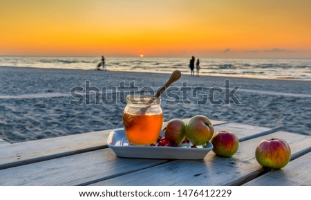 Honey, apples and pomegranate are symbols of Jewish New Year - Rosh ha - Shanah - main Hebrew holiday, food is laying on plate and wooden table, background with defocused sea and colorful sunset #1476412229
