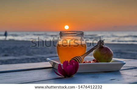 Honey, apples and pomegranate are symbols of Jewish New Year - Rosh ha - Shanah - main Hebrew holiday, food is laying on plate and wooden table, background with defocused sea and colorful sunset #1476412232