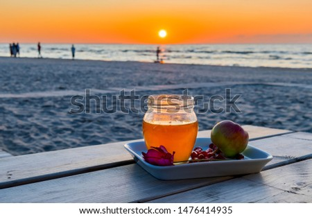 Honey, apples and seeds of pomegranate are symbols of Jewish New Year - Rosh ha - Shanah - one of  the main Hebrew holiday, all attributes are laying on a wooden table, blurred defocused sea  #1476414935