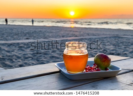Honey, apples and seeds of pomegranate are symbols of Jewish New Year - Rosh ha - Shanah - one of  the main Hebrew holiday, all attributes are laying on a wooden table, blurred defocused sea  #1476415208