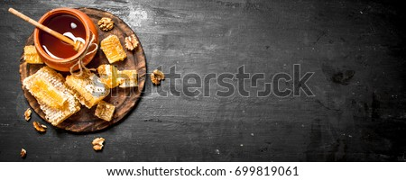 Honey background. Fresh honey in the pot with the nuts. On a black chalkboard.
