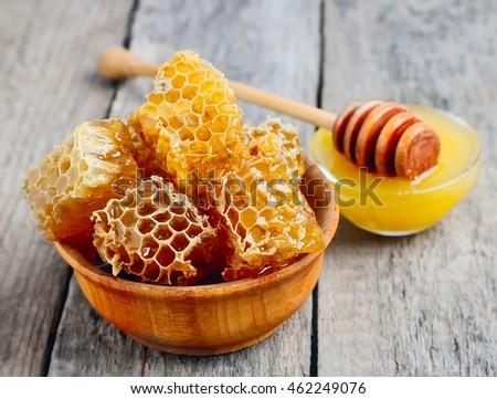 Honey comb honey and liquid honey on the board