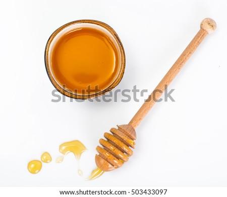 Honey dipper and fragrant honey into a bowl. Studio Photo