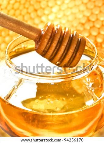 Honey dipper on the bee honeycomb background. Honey tidbit in glass jar and honeycombs wax. - Shutterstock ID 94256170