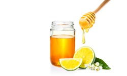honey dipper with honey dripping down, honey jar, and cut fresh lime on isolated white background, room for adding text or copy space