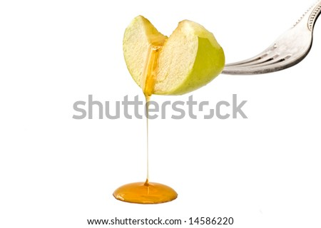 Honey dripping from a green apple slice isolated on white