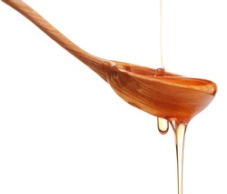 Honey dripping from a wooden honey dipper isolated on white background cutout