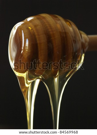 Honey dripping from a wooden honey spoon