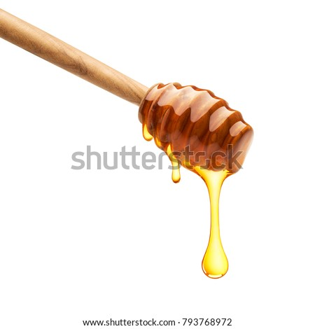 Honey dripping from dipper on isolated white background
