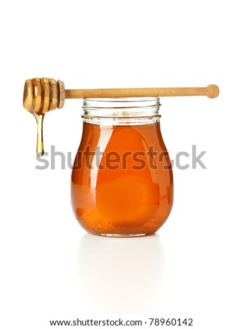 honey dripping from drizzler on top of jar, isolated on white background