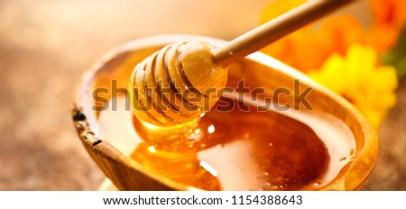 Honey dripping from honey dipper in wooden bowl.  Close-up. Healthy organic Thick honey dipping from the wooden honey spoon, closeup. Sweet dessert background