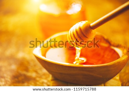 Honey dripping from honey dipper in wooden bowl.  Close-up. Healthy organic Thick honey pouring from the wooden honey spoon, closeup.