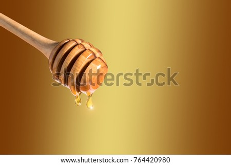 Honey dripping from honey dipper on yellow background. Thick honey dipping from the wooden honey spoon. Healthy food concept.