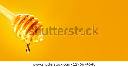 Honey dripping from honey dipper over yellow background. Thick honey dipping from the wooden honey spoon. Healthy food concept, diet, dieting concept. Liquid Syrup, nectar