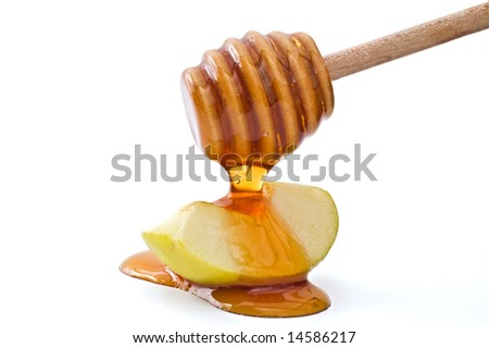 Honey dripping on a green apple slice isolated on white