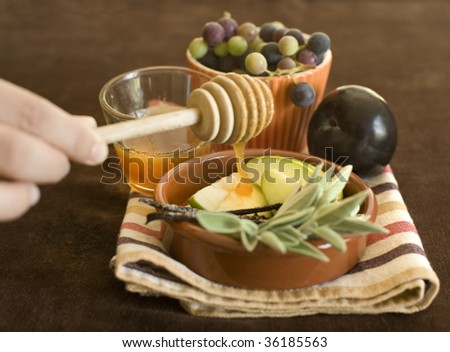 Honey dripping on a green apple slices and other fruits