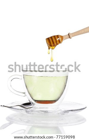 honey drops from a honey dipper in glass cup with green tea on white background