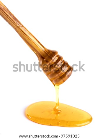 honey flowing down from a wooden honey dipper isolated on white background