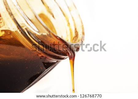 Honey flows from a jar