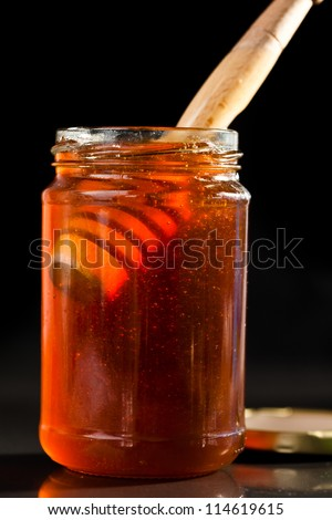 Honey full jar with a honey dipper against a black background