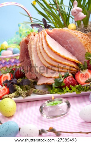 Honey ham on Easter table with eggs, flowers and decoration